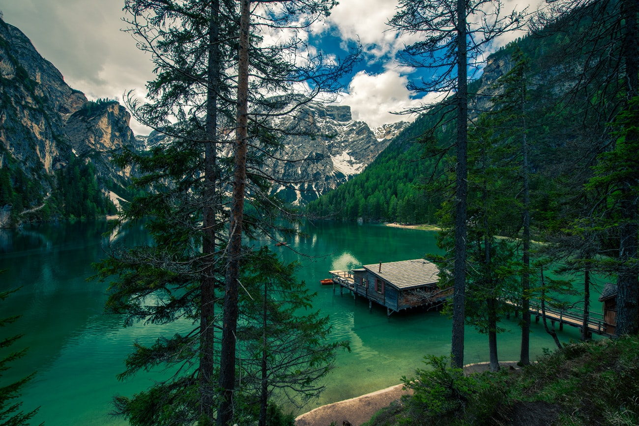 In summer, lake Lago di Braies in South Tyrol reflects colours in all shades from green to blue, in winter Lago di Braies is covered with ice and snow.