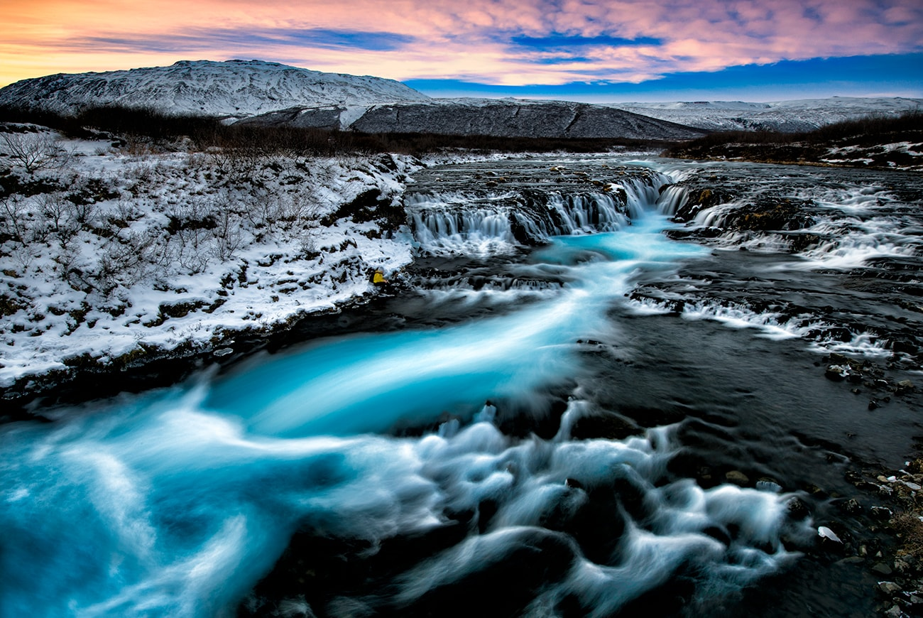 is a relatively small waterfall compared to many of its Icelandic counterparts, but its diminutive size does nothing to take away from its staggering beauty. Both locals and seasoned travellers regard Brúarfoss as one of the country's hidden gems, often labelling it 'Iceland's Bluest Waterfall.'