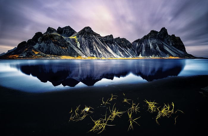 Vestrahorn Iceland is one of the most photographed mountains on the island. Located on the Stokksnes peninsula, its steep slopes reaching a flat lagoon and small black dunes create a natural wonder and one of the most beautiful Icelandic landscapes.