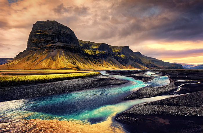 a big mountain with a colorful river in iceland